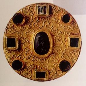 Grossa fibula rotonda con pietre incastonate ad arco finemente lavorato esposta al Museo Nazionale del Medioevo a Roma